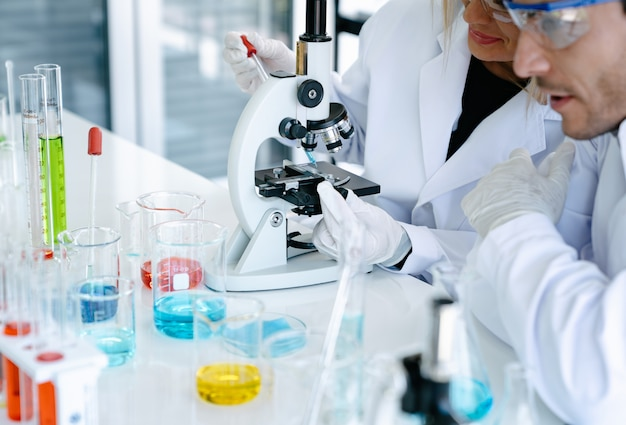 科学者が研究室で医療研究をしながら顕微鏡で薬液をチェック