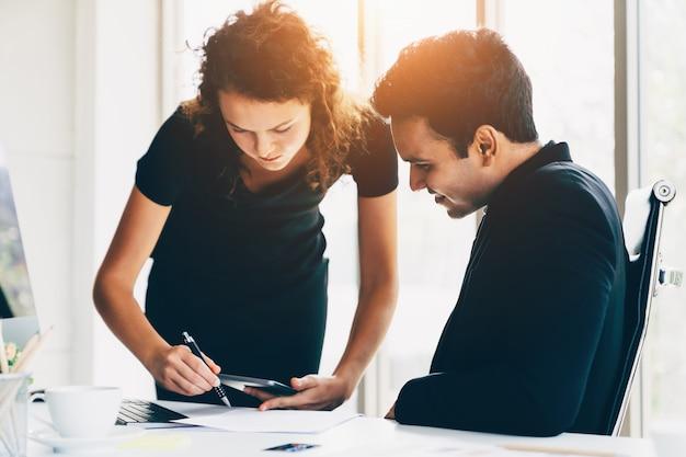 Молодая коммерсантка обсуждая о деле с коллегами команды на листах данных в офисе