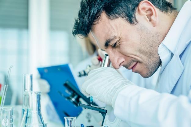 科学者は科学研究室で医学的検査をしながら顕微鏡を調べる