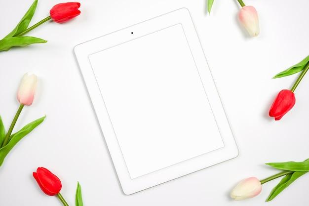 Цифровой планшет белый экран для макета с красивым тюльпаном на белом фоне