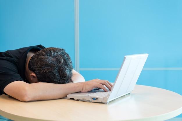 ビジネスマン。昼寝をしたり、仕事に疲れたり、ノートパソコンの前で寝たり、手にかかったりします。
