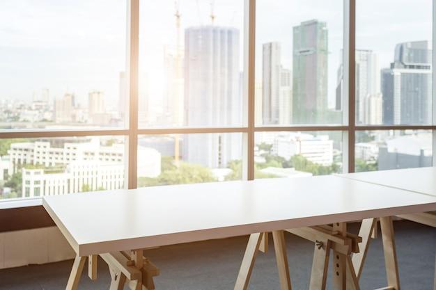 部屋のオフィスと窓のシティビューの背景に空のテーブル。