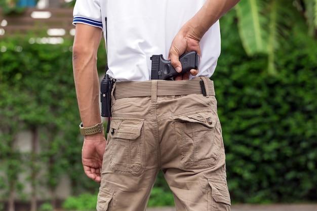 Человек в грузовых штанах с ружьем