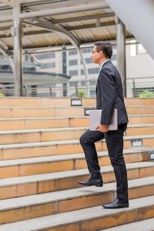 仕事にラッシュアワーの階段を上がる彼のラップトップを持つビジネスマン。急いで時間。