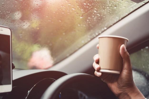 交通機関と車両コンセプト - 車を運転している間に運転手のコーヒーを飲む運転手