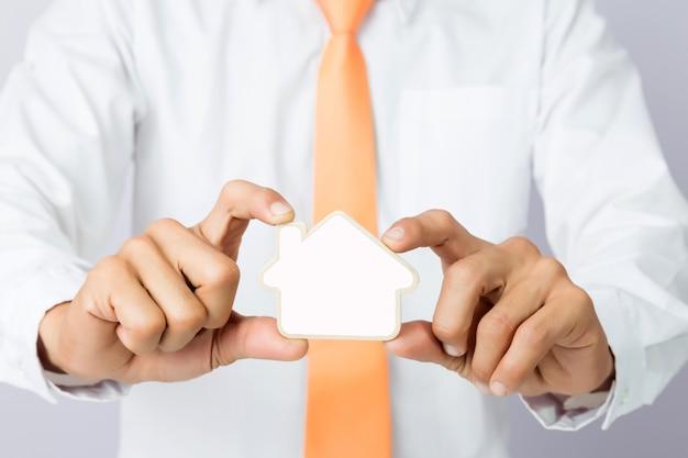 木製のカットハウスの形、隔離された背景を保持するビジネスマンの手