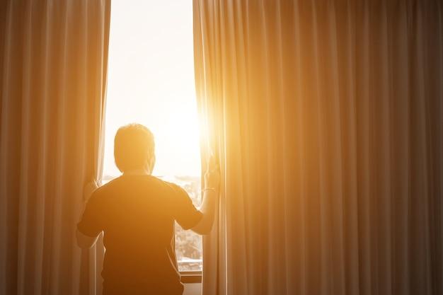 人間と希望のコンセプト。人の窓のカーテンを開く