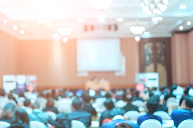 会議室またはセミナーミーティングでの観客のリアビューを備えたステージ上のスピーカー