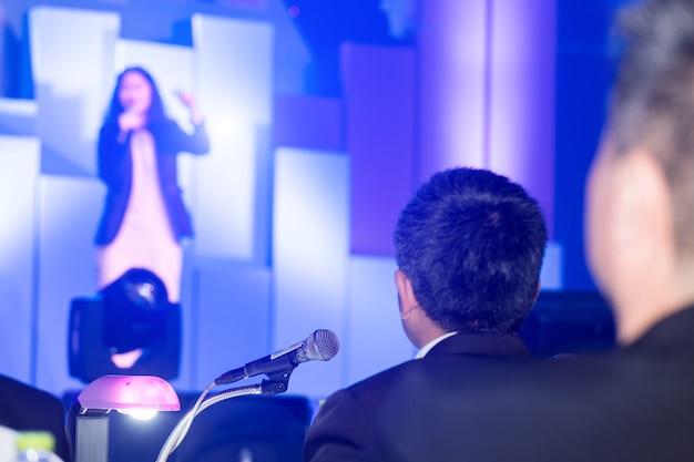 企業のビジネスの話をするスピーカーを見ているビジネスマン