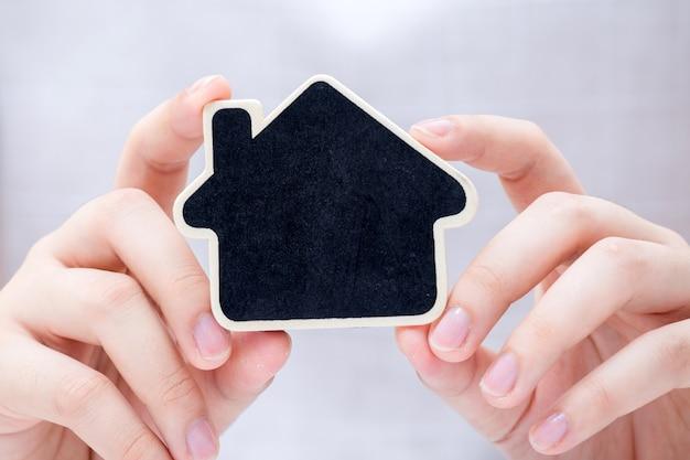小さい家を持っている女性。不動産ビジネスのコンセプト。
