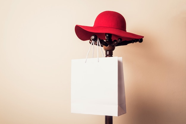 ショッピングバッグと赤い帽子は、木製のハンガーにぶら下がっている