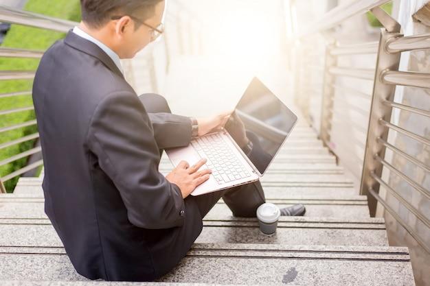 ビジネスマンは、現代の都市で屋外の彼のラップトップで働いています