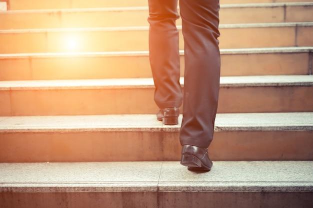 ビジネスマンはラッシュアワーで階段を上って仕事をします。急いで時間。