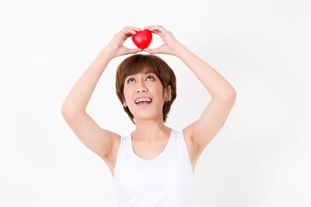 Красивая молодая женщина азии с красным сердцем на голове.