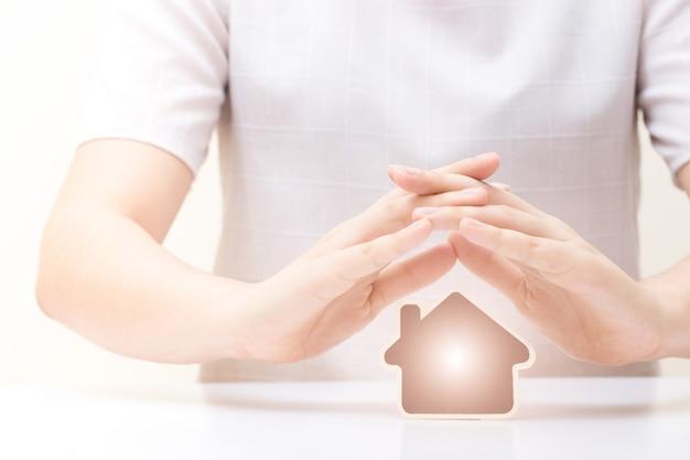 女性の手の下にある家。保険と家の保護概念。