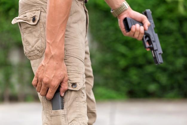 銃を持ったカーゴパンツの男