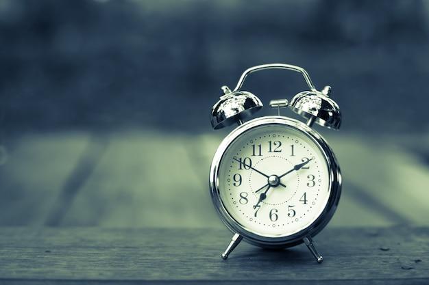 古い木製のテーブルの上にレストロの目覚まし時計
