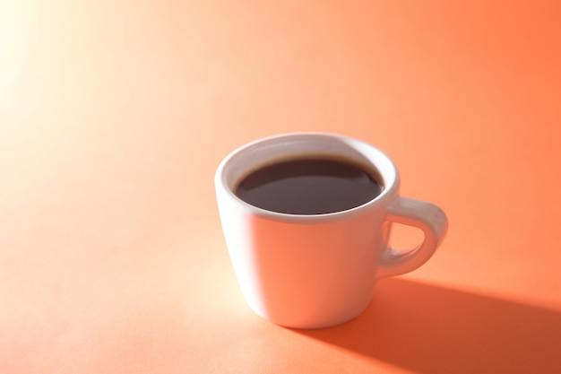 Чашка кофе на оранжевом фоне