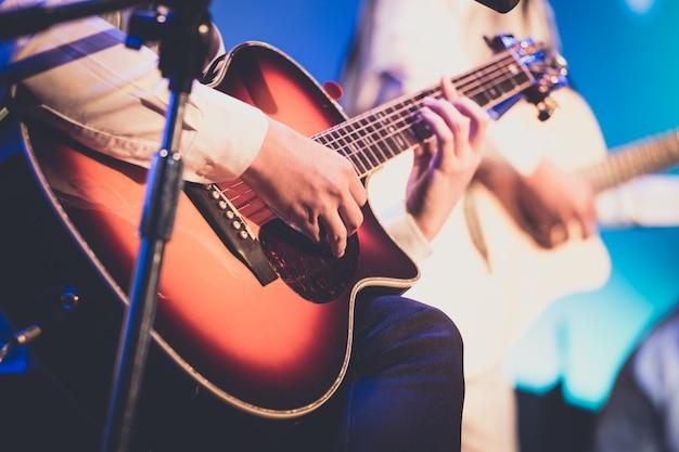 背景のステージ上のギタリスト
