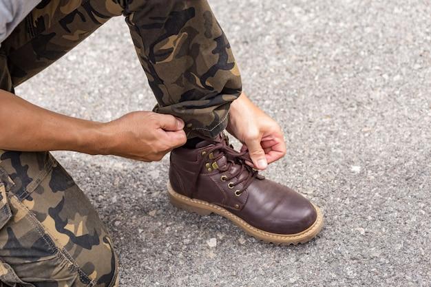 カーゴパンツを着て、革の靴のブーツにひもを結ぶ男