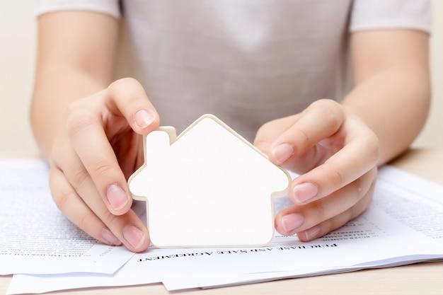 文書の上の小さな家を保持している女性。不動産事業のコンセプトです。