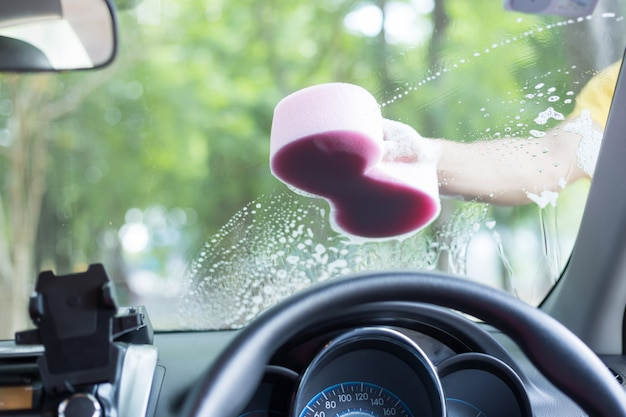 男の手が白い車を洗うためのスポンジを保持します。