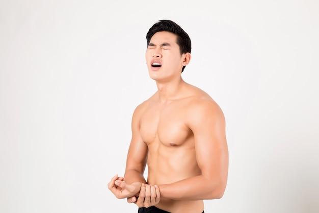 痛みを感じる腕を持つ男。スタジオ撮影白い背景の上。フィットネスと健康の概念