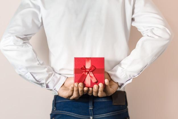 Молодой человек прячет красную подарочную коробку за спиной