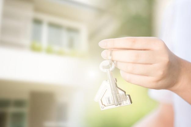 家の鍵を持つ女性の手。不動産事業のコンセプトです。