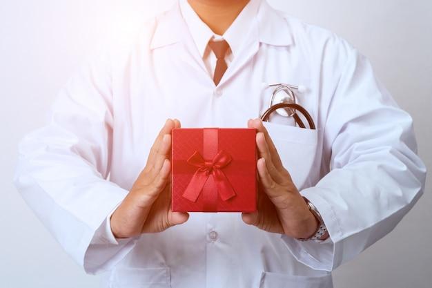 Доктор держит подарочную коробку, здоровый как подарок от доктора