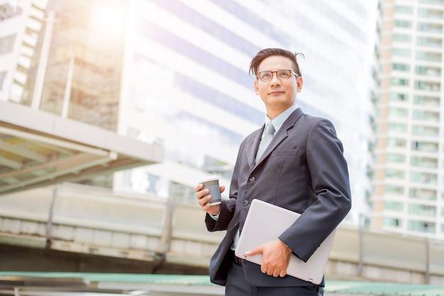 Бизнесмен молодой азии красивый выпивая горячий кофе в современном городе.