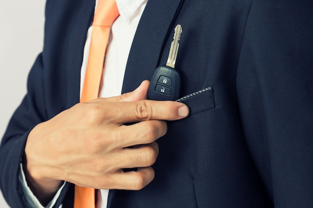 孤立した背景、車のキーを保持している実業家