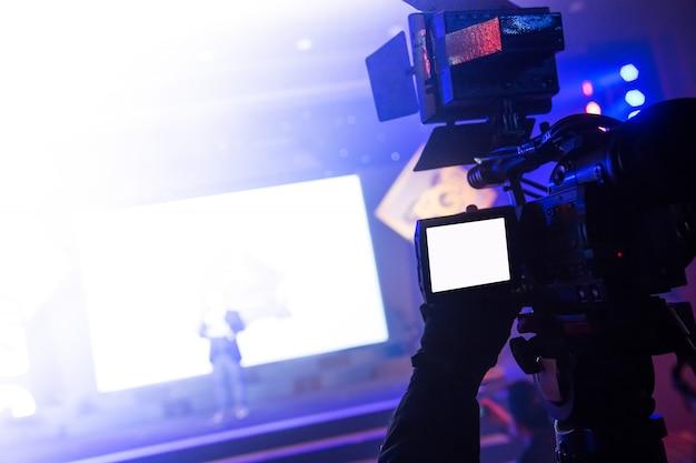 Оператор видеокамеры, работающий на деловой вечеринке