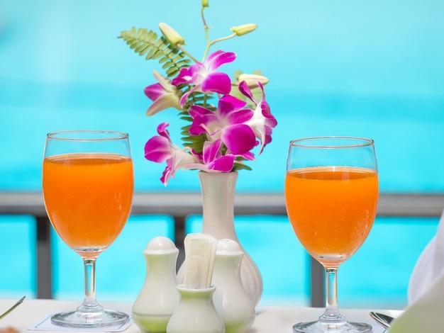 スイミングプールで飲み物の新鮮なオレンジジュース