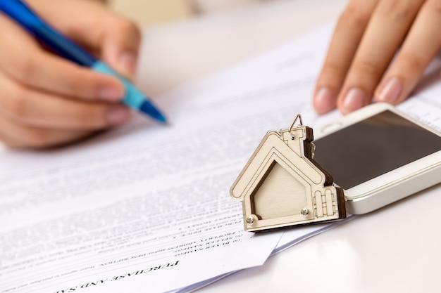 Рука женщины и домашний ключ. подписан договор и ключи от имущества с документами.