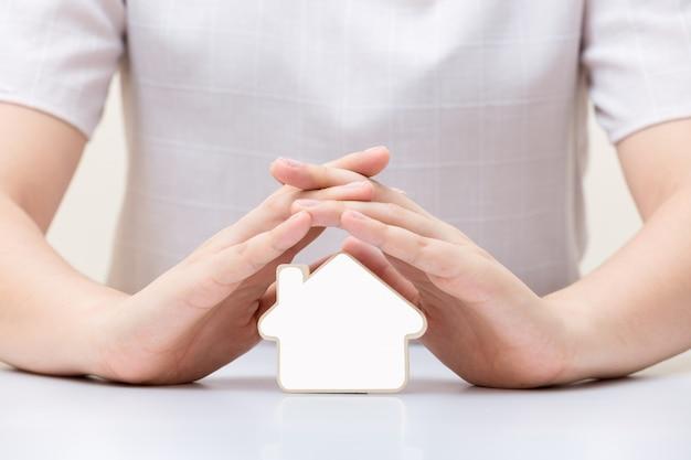 女性の手の下に白い空白の家。保険と家の保護の概念