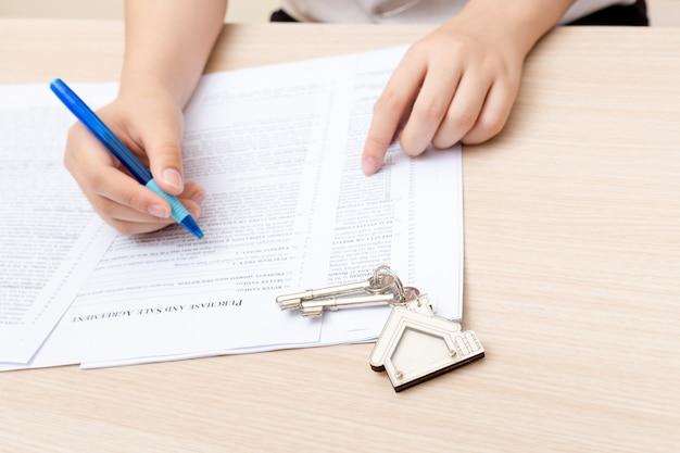 女性の手と家の鍵。文書を使用して契約書とプロパティのキーに署名した。