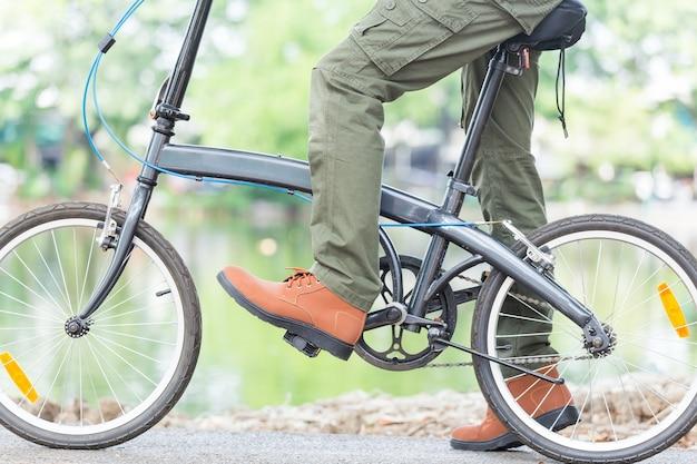 庭で自転車に乗ってカーゴパンツを持つ男