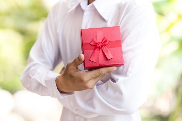 Деловой человек держать красную подарочную коробку в руках.