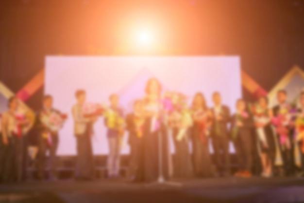 Расфокусировка успеха людей на сцене с освещением на церемонии вручения премии