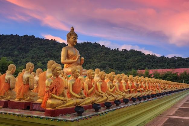 Большая золотая статуя будды и множество маленьких золотых статуй будды, сидящих в ряду в мемориальном парке будды