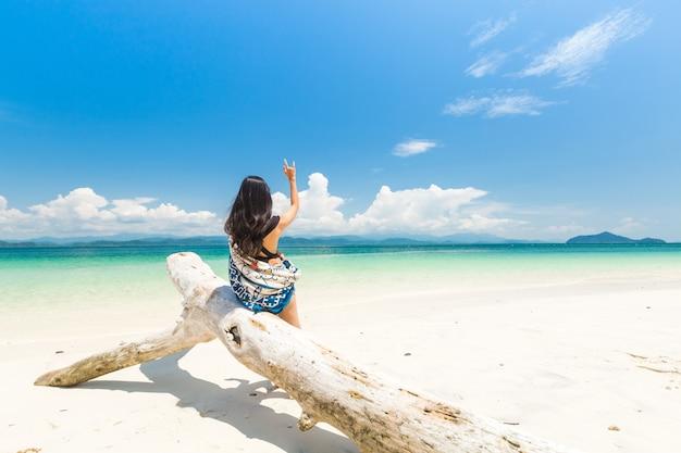 Счастливая девушка на белом песчаном пляже и длинный хвост лодки на острове кханг кхао (остров бат), красивое море ранонг, таиланд.