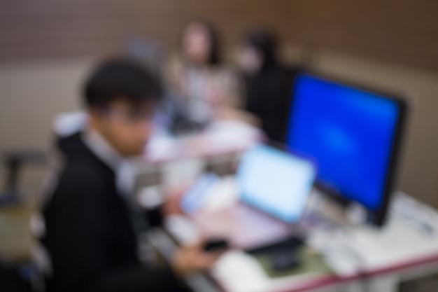 ビジネスマン、近代的なオフィスのコンピューターに取り組んでいるソフトウェア開発者の焦点がずれ