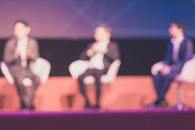会議場やセミナーの会議、ビジネスおよび教育の概念でステージ上のスピーカーの背景をぼかした写真