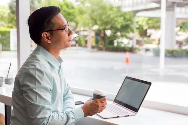 Бизнесмен азии держа горячую кофейную чашку и работая с компьтер-книжкой пока сидящ кафе. концепция молодых бизнесменов