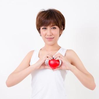 Красивая молодая женщина азии с красным сердцем. изолированные на белом фоне студийное освещение. концепция для здорового.
