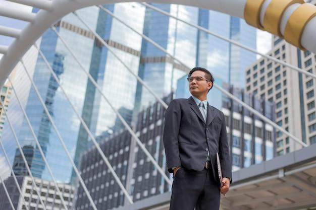 彼のラップトップコンピューターを屋外、背景に近代的な建物との訴訟で若いアジア系のビジネスマン