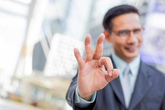 幸せな青年実業家はいいジェスチャーを作る。大丈夫のシンボルです。