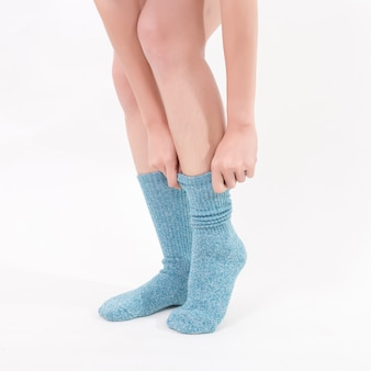 美しい女性の足に青い綿の靴下。白い背景に分離されました。スタジオ照明