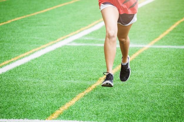 Молодая спортивная девушка работает на спортивной площадке